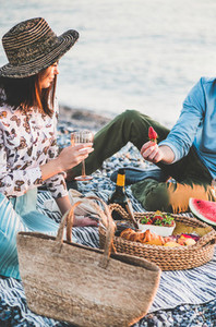 Couple having picnic at seaside with sparklng wine and strawberries
