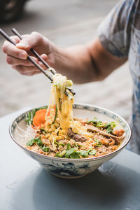 Man eating vietnamese noodle curry with duck from oriental plate