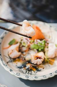 Man eating vietnamese Dim Sum dumplings with chopsticks