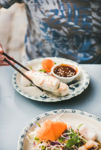 Man eating rice paper rolls with chopsticks in cafe