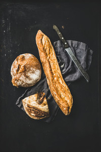 Flat lay of freshly baked baguette and loaf over black background