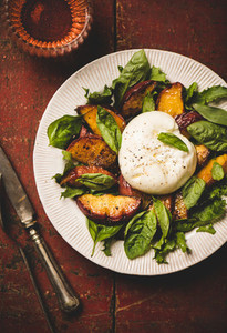 Salad with burrata cheese and peaches and rose wine  close up