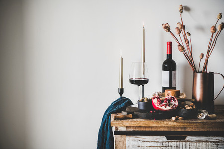 Red wine and snack set over kitchen counter  copy space