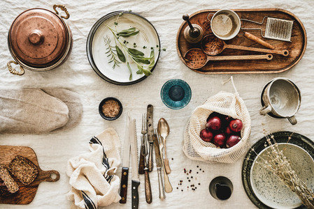 Various kitchen utensils tablewear and fresh bread over linen tablecloth