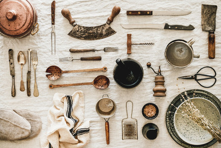 Kitchen utensils and tablewear over linen tablecloth top view
