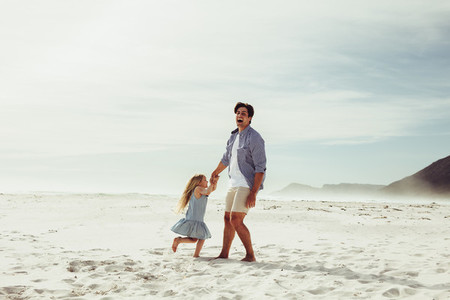 Father and daughter having fun playing on the beach