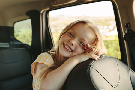 Adorable girl sitting in backseat of car