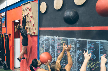 Woman hanging on the climbing wall and classmates doing wall ball