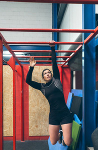 Sportswoman exercising on monkey bars