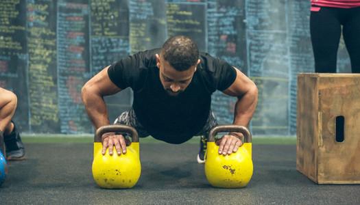 Sportsman doing push ups with kettlebells