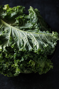 Fresh curly kale salad over dark rustic background