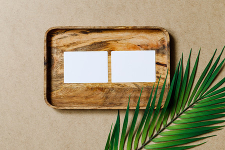 Top view of two blank paper sheet cards on a wooden tray with palm leaf  Tropic mockup for business template  copy space
