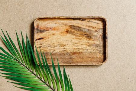 Top view of an empty wooden tray decorated palm leaf