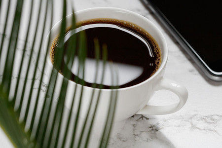 Freshly brewed black coffee  smartphone and a palm leaf on a white marble table