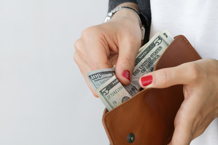 The girl holding an open leather orange slim wallet with cash dollars against white wall