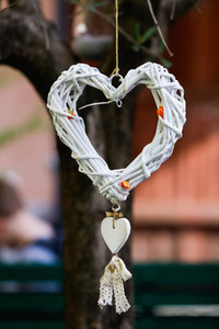 The decorative wicker white heart is hanging on a tree