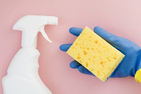 Hand in a blue rubber glove holds a yellow sponge for cleaning on a pink background  Flat lay