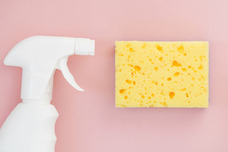 White spray and yellow sponge for washing dishes on a pink background  Copy space  Cleaning concept