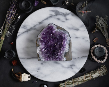 Druze of amethyst stone surrounded magic things on the round white marble tray  View from above