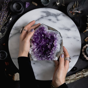 The witch is holding amethyst stone surrounded magic things  View from above