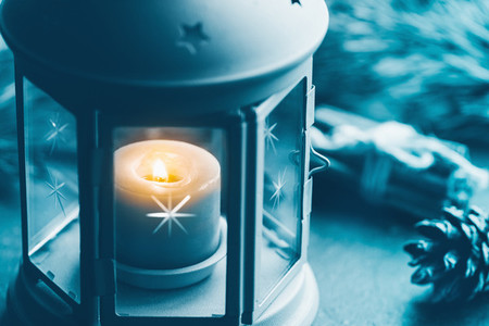 Close up photo of a blue vintage lantern with burning candle among Christmas decoration  Concept of New Year and wintertime