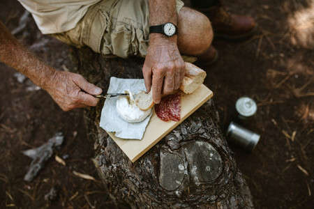 Senior man having food at campsite