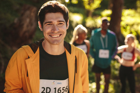 Smiling male runner standing outdoors