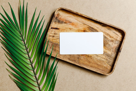 Top view of a blank paper sheet card on a wooden tray with palm leaf Summer mockup for business template copy space
