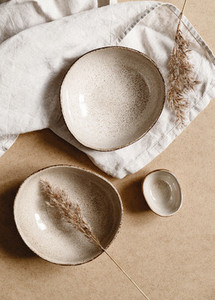 Modern minimalist ceramics set with a linen cloth over kraft paper background  Natural products or food concept  top view  flat lay