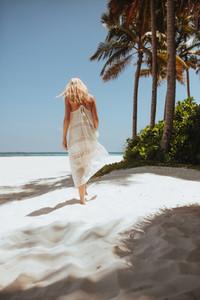 Woman in summer fashion wear at a tropical beach