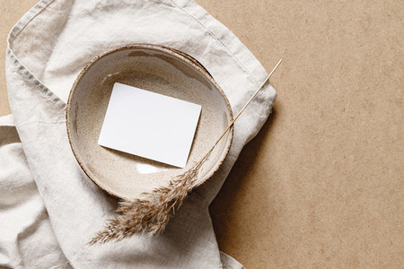Blank paper sheet card in a bowl  Minimalist ceramics set over a linen cloth  Business template  copy space  flat lay