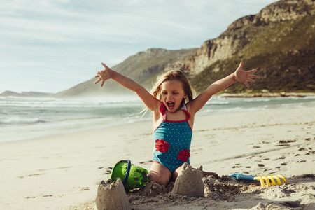 Cute girl making a castle on the beach