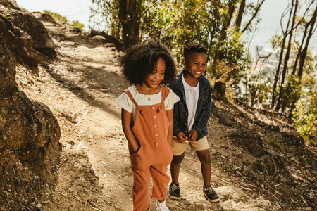 Cute boy and girl walking on a mountain trail