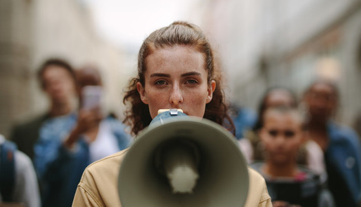 Female activist protesting with megaphone during a strike