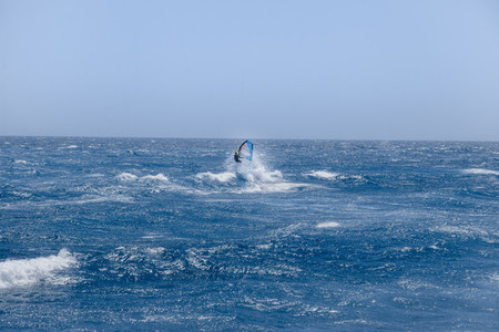 Windsurfer jumping over a wave in the atlantic ocean