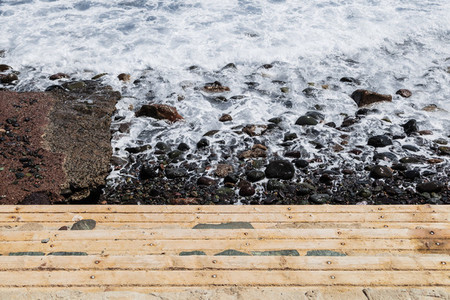 View of wooden stairs on the coast with rocks and sea foam