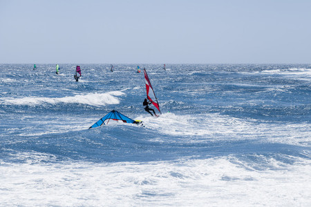 Group of windsurfers practicing in the ocean with colorful sails