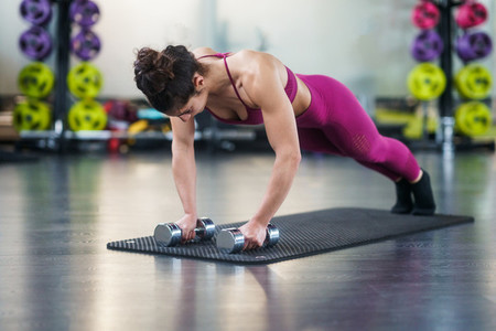 Woman doing push ups exercise with dumbbell in a fitness workout