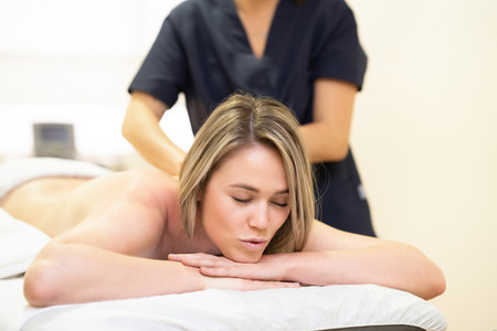 Woman lying on a stretcher receiving a back massage