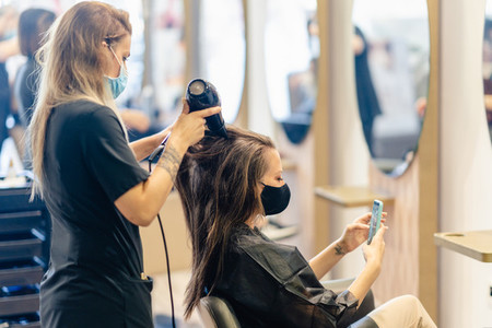 Hairdresser drying her clients hair with a hairdryer wearing protective masks in a beauty centre