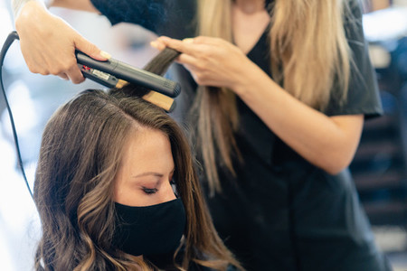 Hairdresser protected by a mask combing her clients hair with a hair iron in a salon