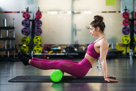 Woman relaxing her leg muscles with a green foam roller