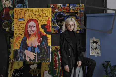 Portrait confident young female artist in studio with paintings