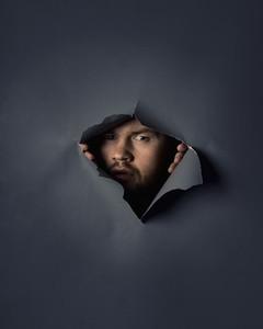 Portrait suspicious man peeking through ripped wallpaper