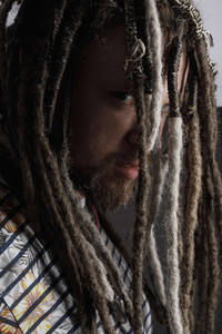Portrait serious man peering through long dreadlocks