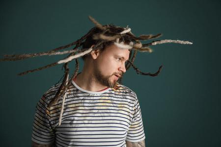 Man with long dreadlocks flipping hair