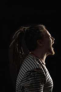 Angry man with dreadlocks screaming against black background