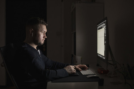 Man with earbuds working late at computer in dark room