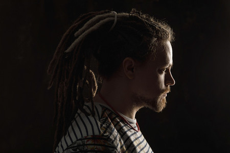 Profile portrait serious  man with beard and dreadlocks