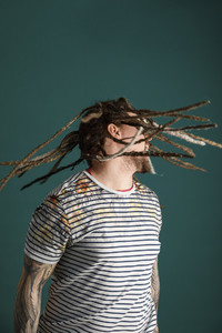 Man with dreadlocks and tattoos flipping hair